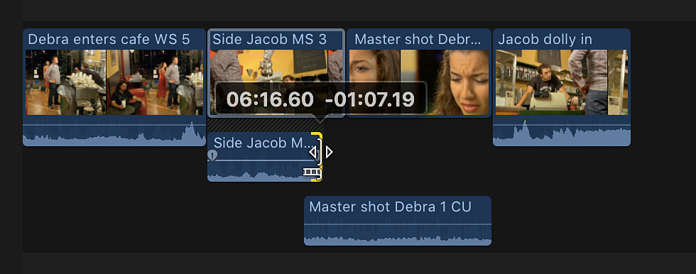 The preceding clip's audio end point being dragged back so that the audio no longer overlaps in the timeline